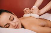 oříznutý pohled na maséra, který provádí masáž s bylinkovým míčem pro ženu v lázních