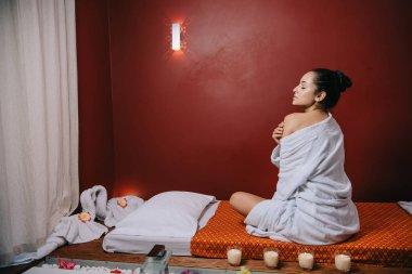 attractive woman in bathrobe sitting on massage mat in spa salon