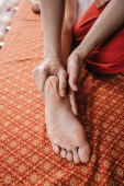 cropped view of masseur doing foot massage to woman in spa salon