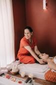 usmívající se asijský masér dělá masáž krku ženě v lázeňském salonu