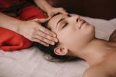 oříznutý pohled na masér dělá masáž tvář ženě v lázeňském salonu