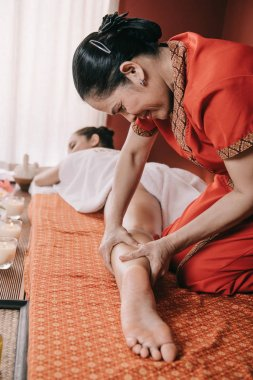 selective focus of asian masseur doing foot massage to woman in spa salon