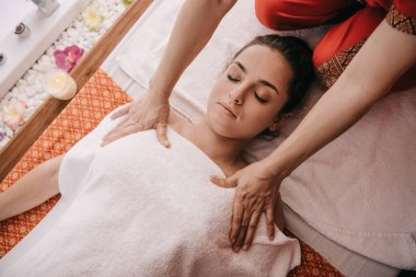 cropped view of masseur doing massage to woman in spa salon