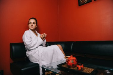 attractive woman in white bathrobe sitting on sofa and holding cup