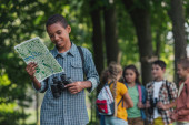 selective focus of happy african american kid looking at map near friends