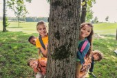 happy multicultural group of kids smiling near tree trunk