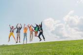 Veselé multikulturní děti skákající a gestikulující proti modré obloze