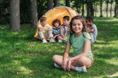 selective focus of cheerful kid sitting on grass near multicultural boys and camp