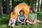 positive and curly boy sitting with cute friends near camp