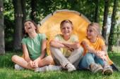 šťastný chlapec, který sedí s roztomilým přáteli v táboře