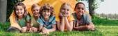 panoramatický záběr šťastných multikulturních dětí s úsměvem v blízkosti tábora