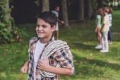 selektivní zaměření veselého chlapce přidržením lana v parku