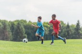 Photo excited multicultural kids playing football on grass