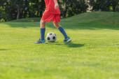 Selektiver Fokus von Kindern in roter Sportbekleidung beim Fußballspielen