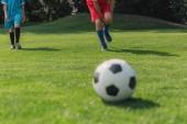 Photo selective focus of boy touching leg near friend near football