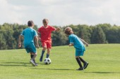 Photo curly boy playing football with friends on green grass