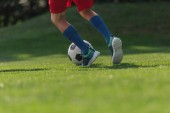 vágott kilátás a gyerek a Sportruházat futó zöld fű a labdarúgás