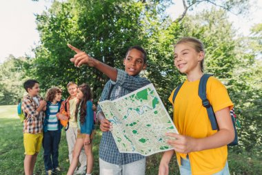 selective focus of african american boy pointing with finger near kid holding map