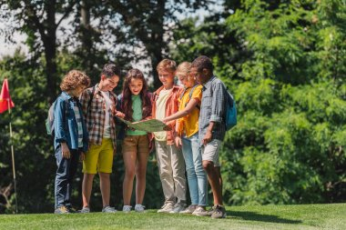 happy group of multicultural kids looking at map near trees in park