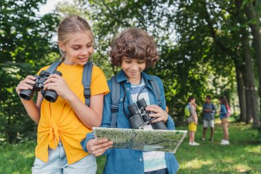 selective focus of happy children with binoculars looking at map