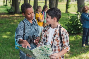 selective focus of african american kid looking at friend with map