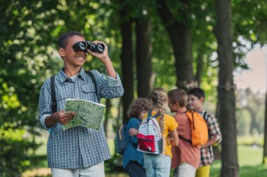 selective focus of happy african american kid looking through binoculars near friends
