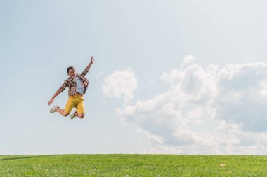 Happy boy jumping and gesturing against blue sky stock vector