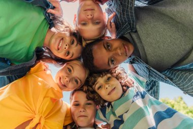 bottom view of happy multicultural kids looking at camera