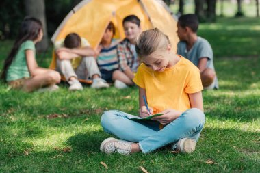 selective focus of happy kid writing in notebook near multicultural friends in camp