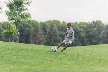 cute african american boy playing football on green grass