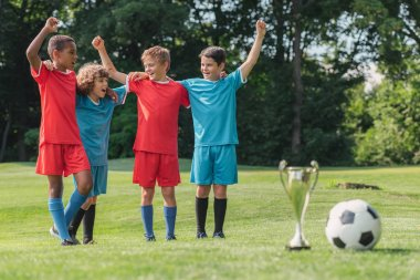 selective focus of multicultural kids gesturing near trophy and football
