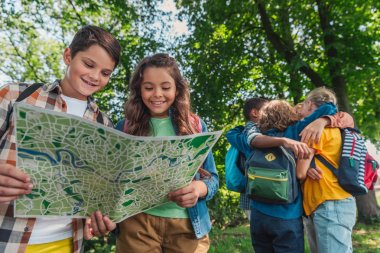 selective focus of happy kids looking at map near multicultural friends hugging in park