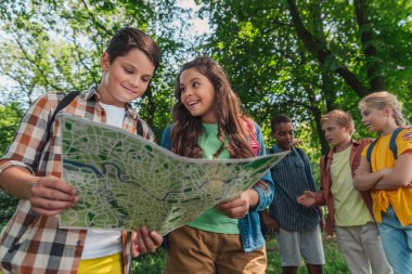 low angle view of cute kid looking at friend and holding map