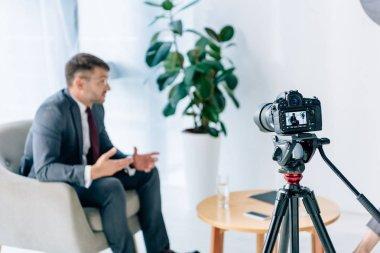 Selective focus of digital camera shooting businessman in office stock vector