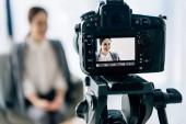 selektivní zaměření kamery na digitální fotoaparát usměvavý novinář v kanceláři