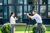 pohled z pohledu atraktivního novináře, který drží mikrofon a kameraman a natáčet ji venku