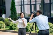 atraktivní novinář držící mikrofon a kameraman, který ji zastřelil