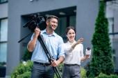 atraktivní novinář držící mikrofon a kameraman přidržený digitální videokameru