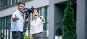 panoramatický záběr atraktivního novináře s mikrofonem a kameramanem přidržením digitální videokamery