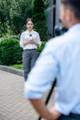selektivní zaměření atraktivního novináře, který drží mikrofon a kameraman a natáčet ji venku