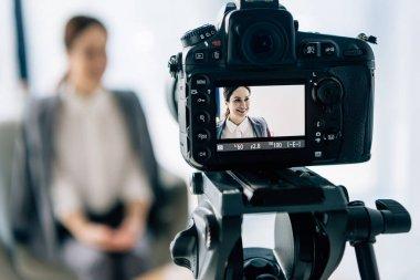 Selective focus of digital camera shooting smiling journalist in office stock vector