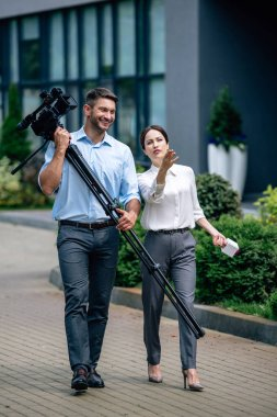 attractive journalist holding microphone and cameraman holding digital video camera