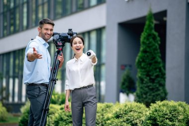 Attractive journalist holding microphone and cameraman holding digital video camera stock vector