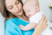 attraktive und junge Mutter hält ihr Kind im Krankenhaus