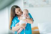 attraktive und lächelnde Mutter hält ihr Kind mit Spielzeug im Krankenhaus