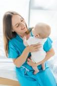přitažlivá a usměvavá matka, držící dítě v nemocnici