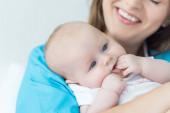 abgeschnittene Ansicht der jungen Mutter, die ihr Kind im Krankenhaus hält