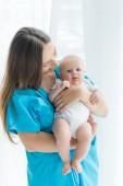 attraktive junge Mutter hält ihr Kind im Krankenhaus