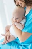 Fotografie abgeschnittene Ansicht der jungen Mutter, die ihr Kind im Krankenhaus hält