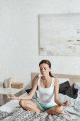 Photo upset young woman sitting on bed in lotus pose with closed eyes